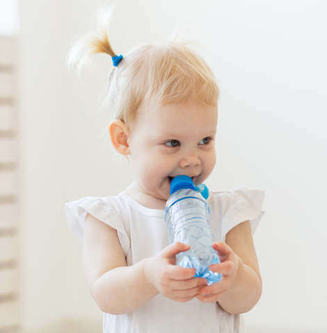 smiling toddler while chewing a bottle of water