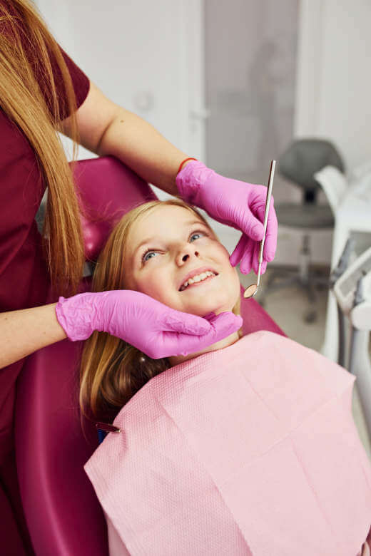 smiling girl sitting at the dentist chair about to receive iv sedation