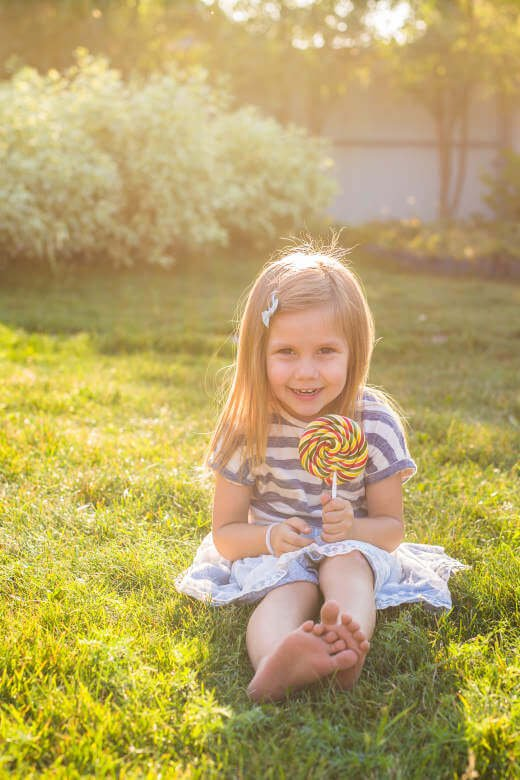 sweet girl licking a lollipop in the yard