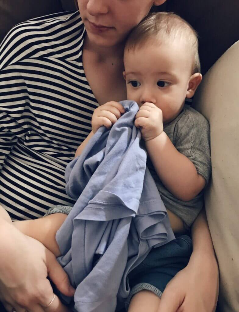 Young toddler is comforted by his mama and sucking his thumb.